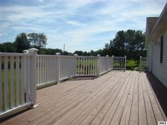 Wood deck with white railings. Beautiful large deck off the back of the house.  Great view.
