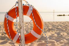 """Orange Life Buoy  New England Living copy this for a wreath! Use 12"""" foam wreath wrapped in orange crepe paper streamers & white duct tape decorate with white rope"""