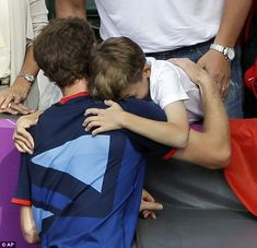 Hug from Murray: The tennis star can't resist the youngster's demand and holds him in celebration after epic win over Federer in the Olympic final