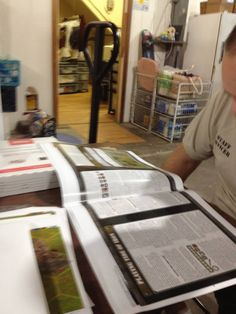 Craig Robertson, Chief Game Developer, looking over the printer proofs for Tide of Iron Next Wave.