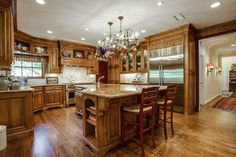 Open brown kitchen // Hug island, two sinks, commercial stainless appliances, hardwoods