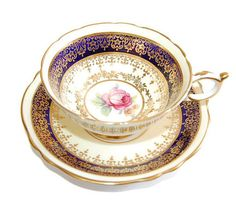Paragon Tea Cup Made in England Bone China 1950s EXCELLENT CONDITION ~ no chips, cracks or repairs Gorgeous cobalt and white tea cup featuring ornate accent trims in gold. Featuring a single pink rose at the center of the cup and saucer, this set makes an elegant choice for tea time and