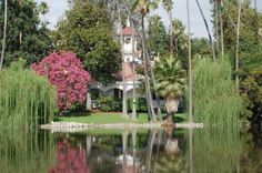 Los Angeles County Arboretum & Botanic Garden.  Queen Anne Cottage - Constructed in 1885, this building is an ornate example of Victorian extravagance. Set in a lakeside landscape featuring prennial color and huge Blue Gum Trees (Eucalyptus globulus). Be sure to look in the windows.