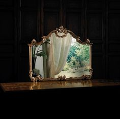 Baroque hand carved overmantel mirror in antiqued gold metal leaf finish.