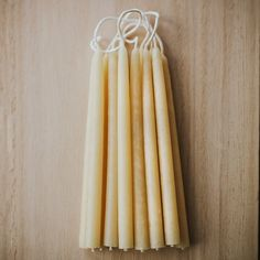 Collection of small beeswax candles lay on a wooden surface.