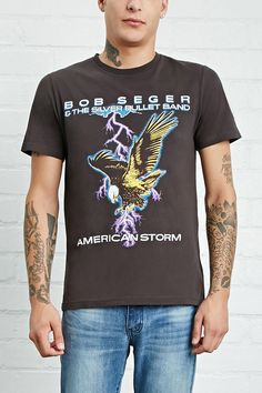 """A cotton knit tee featuring a """"Bob Seger & The Silver Bullet Band American Storm"""" graphic surrounding an bald eagle graphic with lightening bolts on front, an """"American Tour 1986"""" list graphic on back, a crew neckline, and short sleeves."""