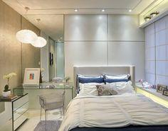 """No Quarto da Moça, projetado por Valéria Loureiro, a predominância do branco, """"quebrado"""" por tons de azul, proporciona tranquilidade e requinte. Materiais como espelhos (que cobrem parte da parede e revestem a cômoda), vidro (na bancada) e acrílico (na cadeira) dão o ar de modernidade à composição."""