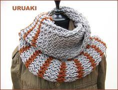 Bufanda gris con rayas marrones y flecos en los extremos.