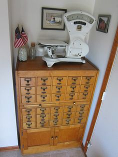 "From ""krislovesfabric,"" a picture of a really unusual card catalog. I've never seen one with a cabinet below. She uses hers for kitchen items. There are a lot more (close-up) pictures at the source; she was using it as a backdrop for photos of things she had made."