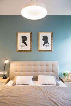 Suite do casal, jogo de cama cinza e branco, parede com tom de azul turquesa, quadros do starwars Princesa Leia e Han Solo. Criados mudos de madeira com portas brancas, luminária preta. Apartamento Contemporâneo em Israel  por Dana Shaked