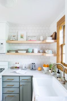 Mint green kitchen cabinets under neutral open kitchen shelves with white tiles against splashes … – White N Black Kitchen Cabinets Mint Green Kitchen, Green Kitchen Cabinets, Kitchen Shelves, Kitchen Storage, Kitchen Dining, Kitchen White, Kitchen Corner, Kitchen Backsplash, White Cabinets