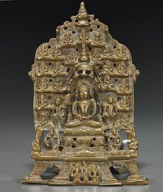 """<b>Antique Indian Brass/Bronze Shrine</b> <br  /> Antique Indian brass/bronze stele-like shrine;  probably <i>Hindu</i> or <i>Jain</i>, with central deity seated on a stepped pedestal and surrounded by many smaller deities or attendants; the central figure with inlaid eyes, inscription to verso (usual wear); H: 6 3/4"""""""