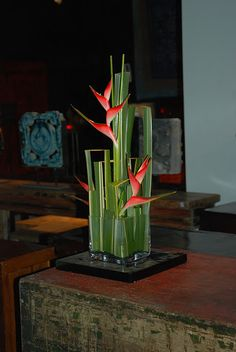 """Cubic Deconstrucción in base of crystal with Phornium variegata. To balance the space I ´ve  added Heliconia caribea. The complete ensamble was made """" to the air """" glues have not been in use in order that Fornium's foliage does not lose naturalness off."""