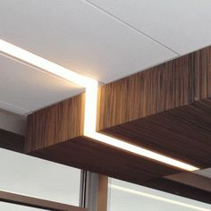 lighting detail - linear light fixture wrapping around a wood veneer soffit