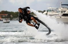Sean Phillips flies through the air as he demonstrates the JetLev water-propelled jet pack strapped to his back at the Yacht & Brokerage Show on February 17, 2012 in Miami Beach