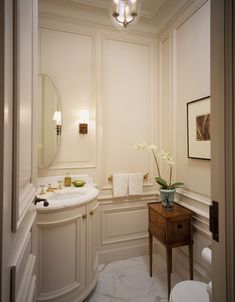 Make full use of the limited space in a powder room by installing a vanity to fit in the corner. The mood lighting and flowers adds atmosphere for guests.