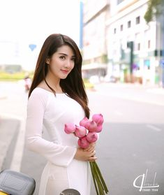 Hot girl Sài thành diện áo dài trắng, khoe sắc bên sen hồng và dạo chơi giữa phố xuân.