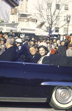 In a photograph that, five decades later, feels at once haunted and familiar, a smiling President and First Lady ride through cheering crowds in the inaugural parade, their very clothes evoking a similar sunny scene enacted less than three years later, in Dallas. http://en.wikipedia.org/wiki/Assassination_of_John_F._Kennedy  http://en.wikipedia.org/wiki/Timeline_of_the_John_F._Kennedy_assassination