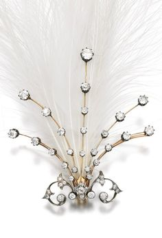An Edwardian diamond and feather aigrette, 1900s. Of spray design, set with circular-cut diamonds, holding a plume of white egret feathers, detachable brooch, tiara, and tortoiseshell comb fittings, fitted box stamped Collingwood & Co.