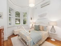 Lovely bedroom with bay window with plantation shutters, feature ceiling, feature cornices, wide skirting boards and timber floor. #bedrooms #ceilings #cornices #timberflooring #windows #plantationshutters