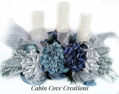 This beautiful Peacock Candleholder Centerpiece/Floral Arrangement will really make your space pop this Christmas and Holiday season. This one of a kind design features: *glitsy poinsettias in variating blue/teal and olive green edged edged in gold *peacock feather picks with glitzy sprays *glitzy grape cluster and berry picks in shades of purple, royal blue, turquoise, and lime green *2 metallic bows in turquoise *deco mesh in royal blue *stemmed ornament picks in foiled aqua and royal…