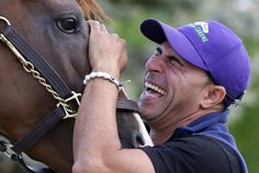 Exercise rider Willie Delgado laughs as he waits to guide Kentucky Derby and Preakness winner California Chrome onto a trailer at Pimlico Race Course in Baltimore, Tuesday, May 20, 2014. The horse is headed to Belmont Park in Elmont, N.Y, where the Belmont Stakes horse race is scheduled to take place June 7.