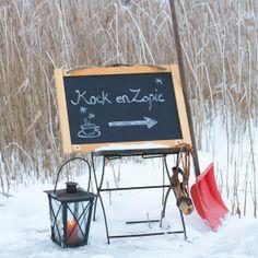 Zet op het podium een krijtbord met daarop 'koek en zopie' geschreven. Leuk aangekleed met een lantaarn en een paar schaatsen maakt het plaatje af.