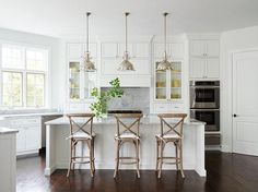 Absolutely gorgeous kitchen features three Restoration Hardware Harmon Pendants illuminating a white center island topped with White Fantasy Quartzite lined with three French x back counter stools.