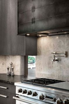 Hood and Color of cabinets A black metal range hood is flanked by dark gray modern cabinets mounted in front of windows. Kitchen Island Hood Ideas, Kitchen Hood Design, Modern Kitchen Backsplash, Kitchen Vent, Kitchen Hoods, Kitchen Decor, Mountain Modern, Modern Cabinets, Metal Kitchen Cabinets
