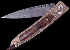 The Ventana 'Katsumi' features a beautiful frame in 'Raindrop' Mokume Gane by Mike Sakmar, inlaid with a mesmerizing piece of fossil dinosaur bone, the only remaining legacy of an Apatosaurus that walked the earth 100 million years ago. The blade is hand-forged 'Typhoon' damascus by Rob Thomas; the two-hand button lock is set with white topaz.