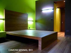Camera minimal bio, letto costruito in opera e rivestito con il parquet del pavimento. Il contenitore si fonde con il contenuto.