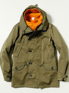 ten c F/W14 Outerwear   Timeless military silhouettes alongside new modular liner options and headwear accessories. Deck Parka Olive paired with Wool Hood Felt Orange.