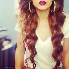 Long, wavy hair with a bold purple lip