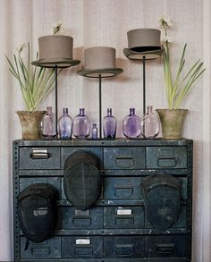 Vintage blue metal cabinet, many drawers with metal label holders, top hats on tall hat stands with clear violet vintage jars interspersed, flanked with 2 tall pots of paperwhites  Brooke Giannetti. Giannetti Home.