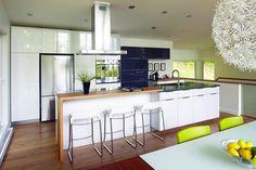 6- cuisine avec tabouret blanc, comptoir en bois et électro en inox
