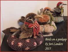 All my bird pin-keeps are made with a combination of needle felting and stitching with mohair, wet felted wool, and vintage wool. Real feathers are used on many. The birds are snapped to the cushion and can be removed. The cushion fabrics are repro civil war fabrics. $225 a piece.