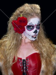 close-up portrait of a scary woman in traditional folk art. - Close-up shot of a scary female posing in sugar skull make-up against dark background. Model: Christine Vandenberk