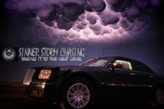 Chrysler 300 Storm Chase Vehicle With Lightning Illuminate Mammatus Clouds In The Back Ground