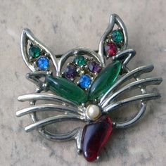 Beautiful Bejeweled face cat brooch with green red blue pink diamante This vintage cat jewellery is very much in the Swoboda style but is unsigned on