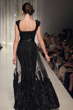 TONY WARD - Black sequined evening dress covered by tulle embroidered on the sleeves and at the bottom with satin ribbons of different sizes.