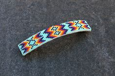 """Hand made Navajo Beaded Barrette  Native American Beadwork  Beautiful hand beaded barrette. Great colors that compliment the feather design. Tiny seed beads are used and backed with soft leather.  5/8"""" wide x 3 1/2"""" long  When trade beads were introduced to Native Americans, they made these colorful glass beads part of their jewelry. Over the years, glass beads have been used to complement traditional designs and to adorn everything from clothing to ceremonial objects. Artists from the…"""