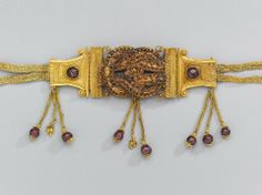 A diadem (or headband) worn over a high female coiffure. The center is composed of a Herakles knot, whose strands are garlands of pointed leavees; a rosette, once inlaid with a stone, marks the center of the knot. The Herakles knot is hinged to sofa-capital-shaped plates,200-150 BC