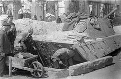 A Panther V Ausf G is being dig in as a fortified defensive position on a Berlin street corner diring 1945