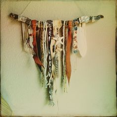Gypsy wall art using leather scraps, wool, earthy textured string, hippie fabric, beaded stones, sea shells, and feathers, hung off of a stick.