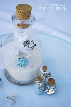 starry night baby shower - decor: centerpieces created with a variety of clear glass bottles filled with white sand and glitter