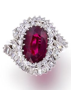 A ruby and diamond ring  centering an oval-shaped ruby, within a surround of single-cut diamonds and further swirl of baguette and marquise-shaped diamonds