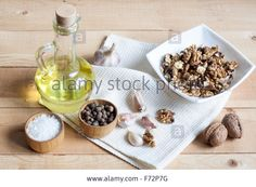 Download this stock image: Food ingredients. Oil, eggs, garlic, limon, walnuts and herbs on wooden table. Wooden board and napkin. - F72P7G from Alamy's library of millions of high resolution stock photos, illustrations and vectors.
