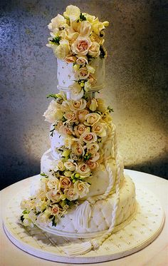 Tiered cake, covered with quilted fondant, fresh flowers and a white chocolate rope