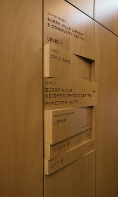 Wood signage, shifting panels, wood burned/engraved names lobby directory Sydney library and community center