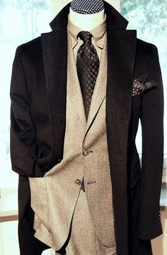 A grey suit with a black coat. A combination that is not too common, but boy does it look great!